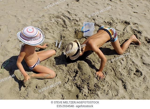 A boy and girl at play on the beach of Grau d'Agde, France