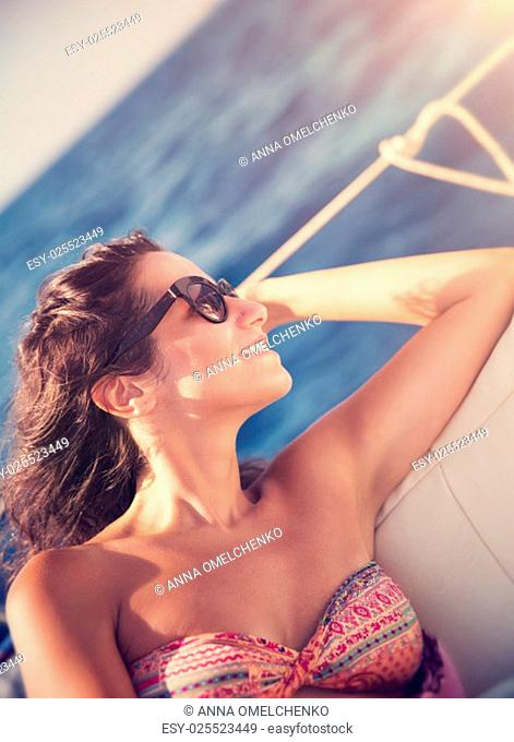 Beautiful brunette woman relaxing on sailboat, sitting on the deck and enjoying bright sun light, luxury summer vacation on water transport