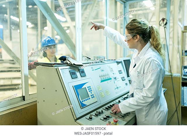 Female colleagues working at control panel in a factory