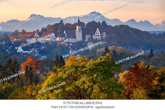 17 October 2019, Baden-Wuerttemberg, Riedlingen: Neufra Castle and the parish church of St. Peter and Paul are illuminated by the rising sun