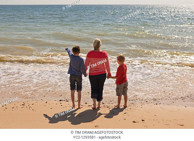 Mother and two sons stand on a UK beach looking out to sea in the summer