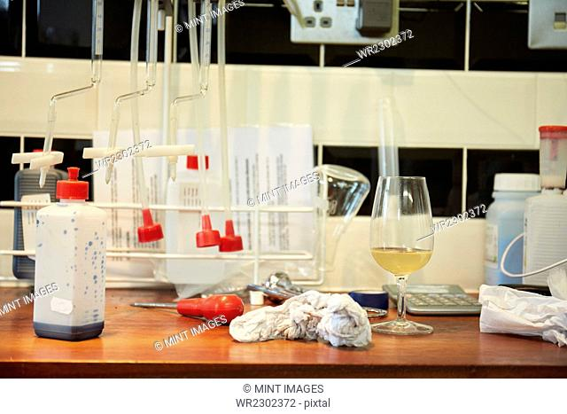 A winery laboratory. A worktop with flasks and tubes, a glass of wine and a screwdriver