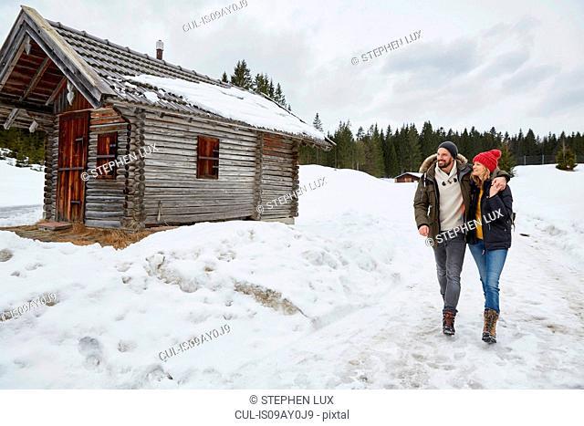 Couple hiking from log cabin in winter, Elmau, Bavaria, Germany