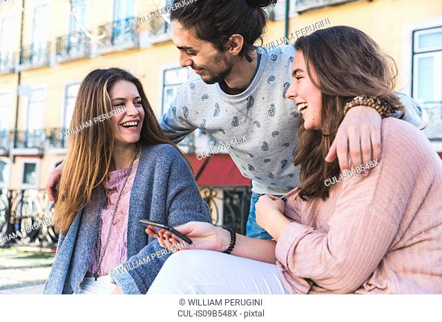 Three friends, outdoors, laughing, young woman holding smartphone, Lisbon, Portugal