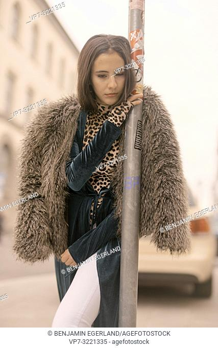 exhausted woman leaning on lamppost at street in city, tired, sleepy, Munich, Germany
