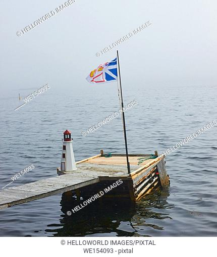 Small wooden pier jetty with model of a lighthouse and the Newfoundland and Labrador flag, Newfoundland, Canada