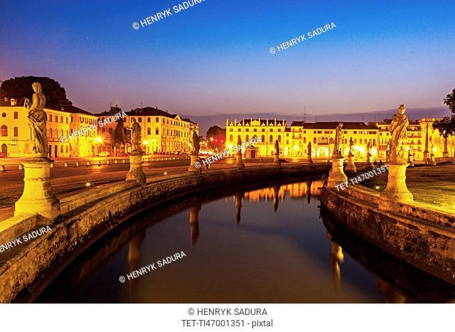 Illuminated Prato della Valle with statues at dusk