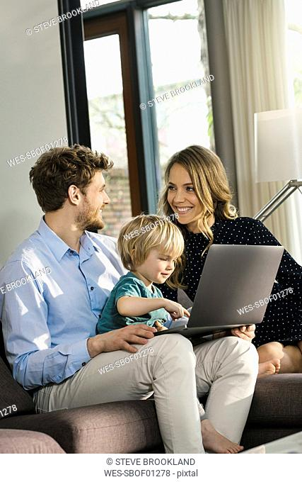 Smiling parents and son sitting on sofa with laptop at home