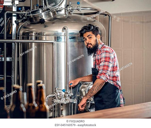 Indian bearded tattooed hipster male manufacturer presenting craft beer in the microbrewery