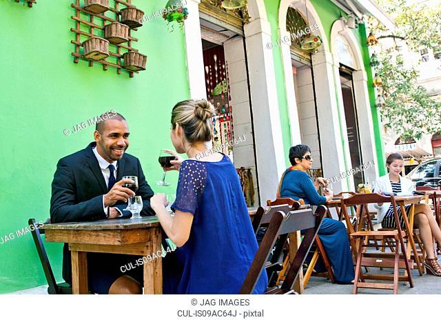 Couple having wine outside cafe