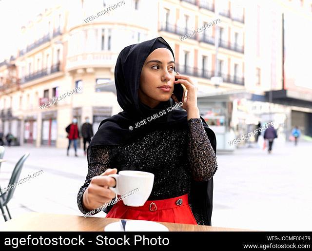 Portrait of young beautiful woman wearing black¶ÿhijab¶ÿusing smart phone at sidewalk cafe