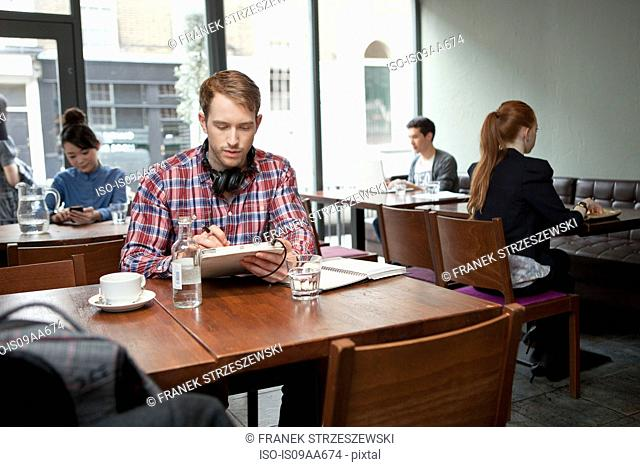 Young man with digital tablet in cafe