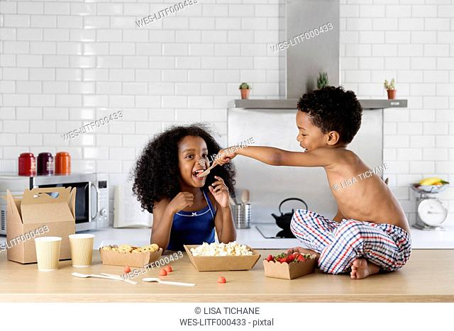 Brother feeding his sister with a spoon