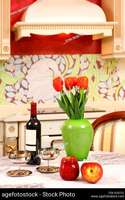 the wine bottle, two glasses, apples and bouquet of tulips in a green vase on a kitchen table