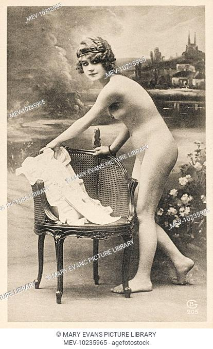 A young naked woman reaches for her corset on the chair beside her