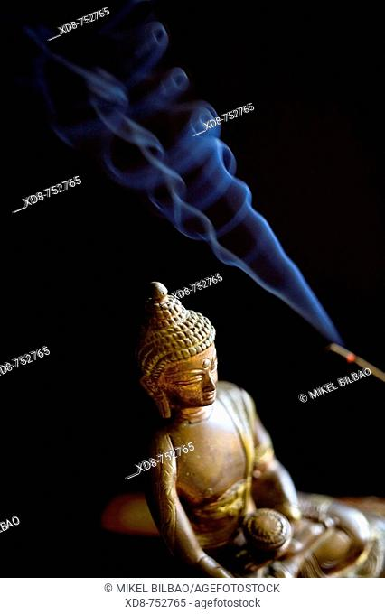 Buddha little statue with incense sticks