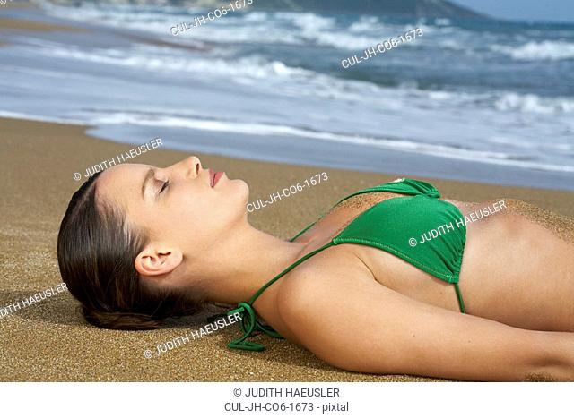 Young woman in bikini on beach lying in sand eyes closed sea in background