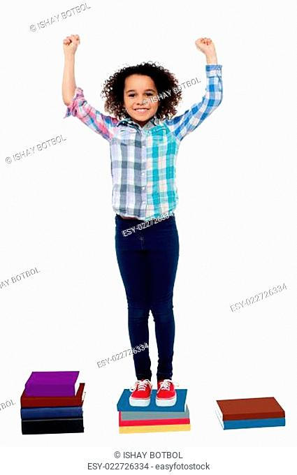 Excited pretty school child standing on books
