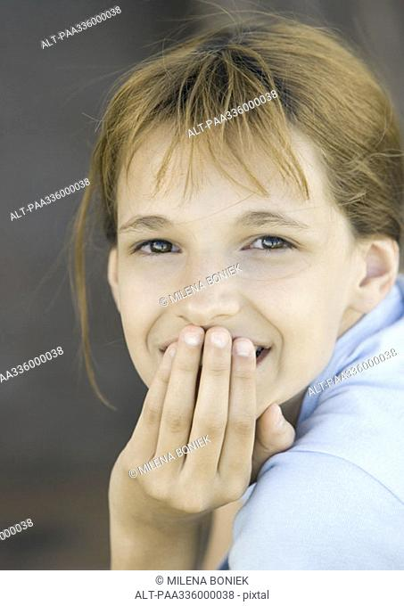 Girl covering mouth looking at camera, smiling, portrait, close-up