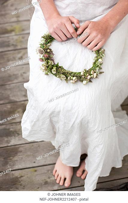 Woman holding flowers wreath
