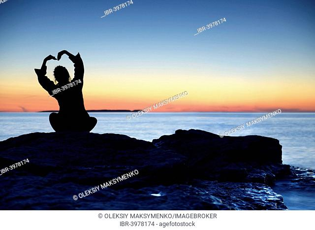 Silhouette of a woman sitting on a shore at sunset with her hands raised above her head, Georgian Bay, Ontario, Canada