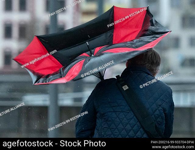16 February 2020, North Rhine-Westphalia, Dortmund: The umbrella of a walker is folded down at Lake Phoenix because of a gust of wind