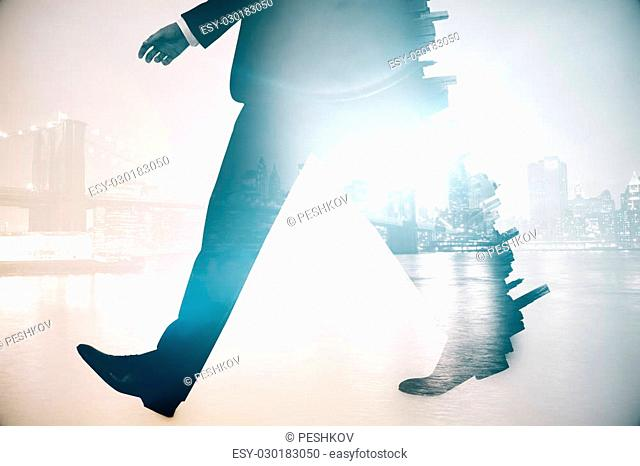 Legs of walking businessman in suit on abstract city background. Double exposure
