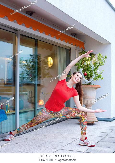 woman exercises yoga outdoor on a terrace