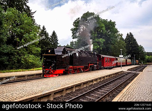 Old steam locomotive leaving the train station with smoke coming out of the chimney