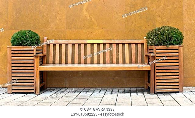 Wooden bench with bush in front of marble wall