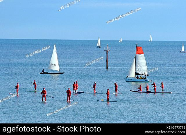 Santa Claus in paddle surf and sail boats in front of the beaches of Barcelona, Catalonia, Spain