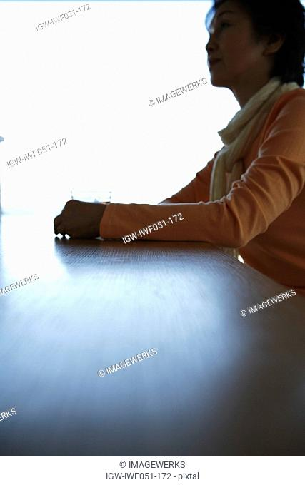 Senior woman sitting by table