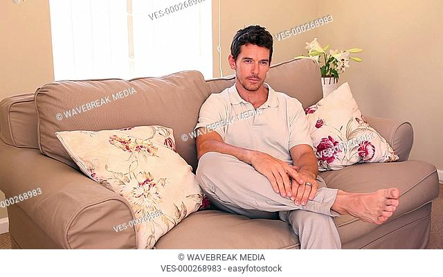 Woman sitting down on couch covering her boyfriends eyes