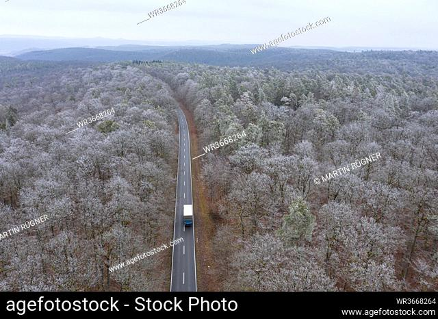 Germany, Bavaria, Drone view of truck driving along asphalt road cutting through Steigerwald forest in winter