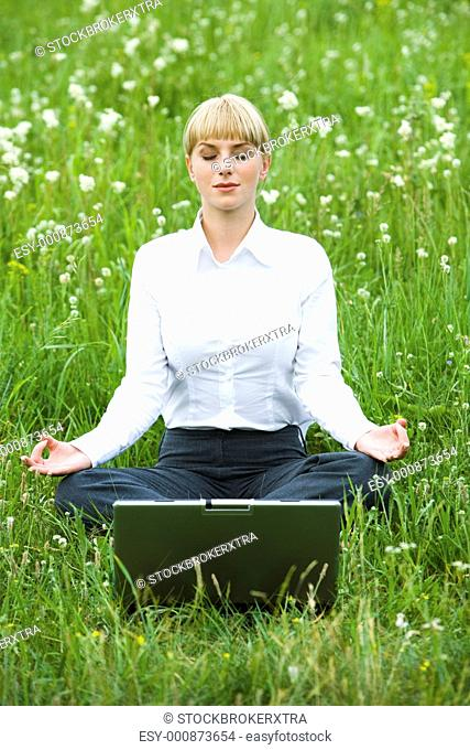 Portrait of businesswoman sitting on the grass and meditating