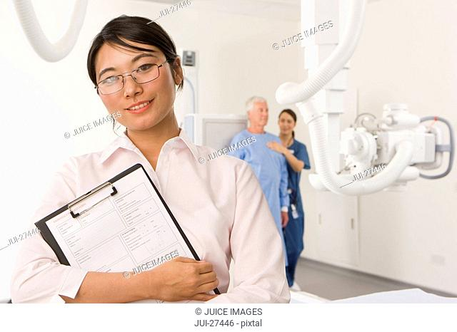 Radiologists helping patient with x-ray machine