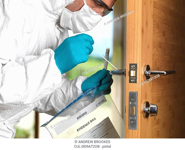 Forensic officer taking DNA swab off door handle