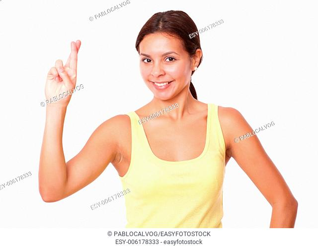Portrait of cute latin girl on yellow t-shirt with luck sign smiling at you on isolated white background