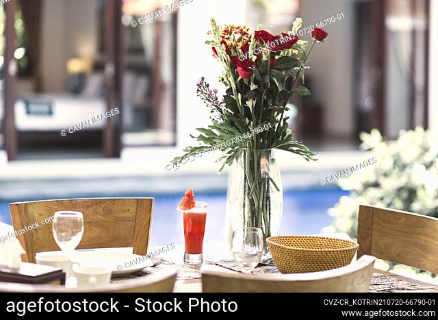 Flower bouquet at the table and pool in background