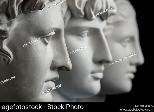 White gypsum copy of ancient statue of Apollo, Antinous and Venus head for artists on a dark textured background. Plaster sculpture of statue face