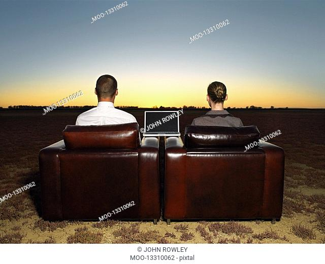 Two business people sitting in armchairs in open plain at sunset back view