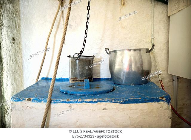 Water well hole painted blue with a bucket to draw water and a pot, from a fishing lodge. Sa Mesquida, Mahó, Minorca, Balearic Islands, Spain