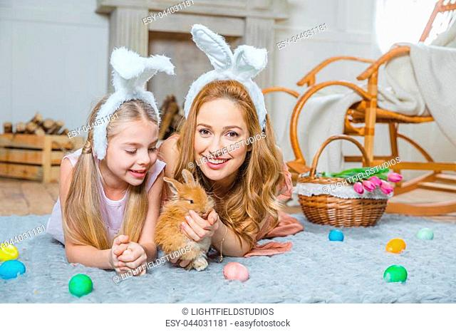 Mother and daughter wearing bunny ears and playing with rabbit at home