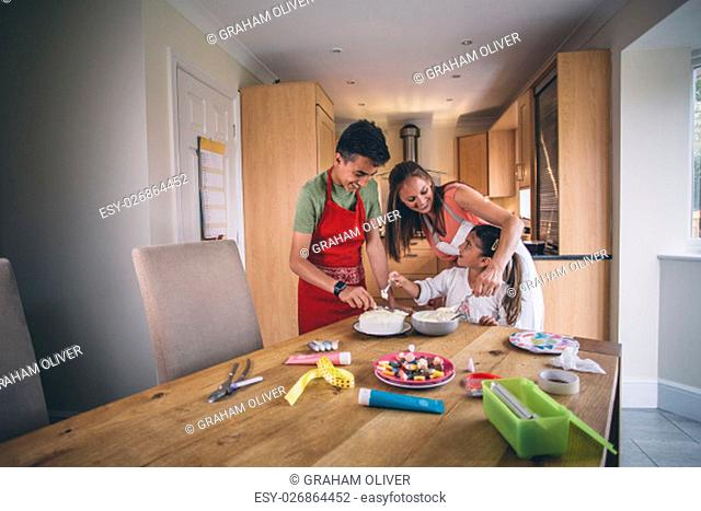 Mother helping her son and daughter to decorate a cake in the kitchen of their home