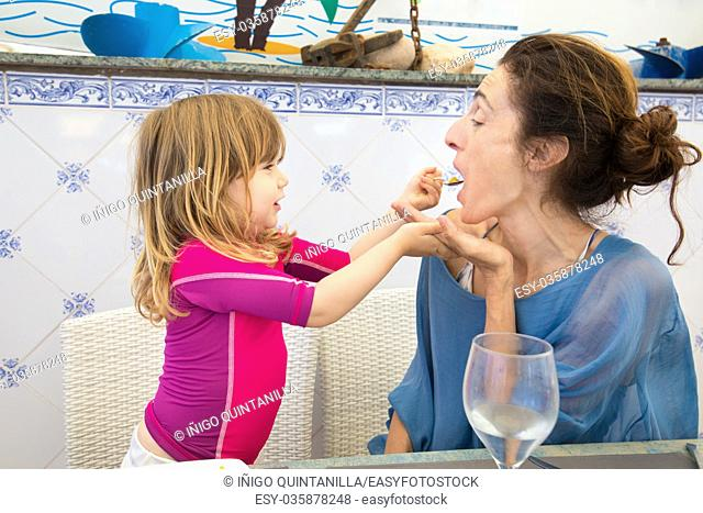 funny scene of three years old blonde child feeding paella rice with spoon to woman mother sitting in restaurant, happy and laughing