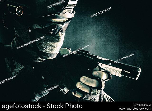 Army counter-terrorism squad, police SWAT team fighter hiding identity behind mask and glasses, wearing helmet with night vision-device, creeping in darkness