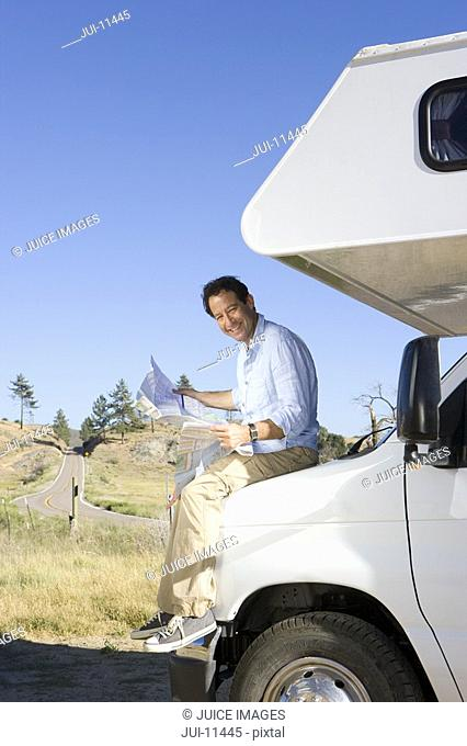 Man on front of motor home looking at map, smiling, portrait, low angle view