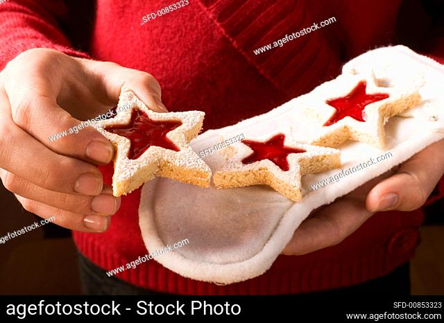 Hands holding jam biscuits on white boot