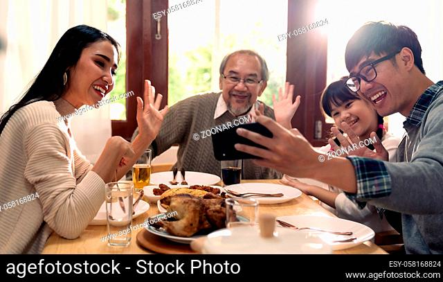 Happy asian multigenerational family of dad mom daughter girl and grandfather taking selfie together before eating lunch together at home