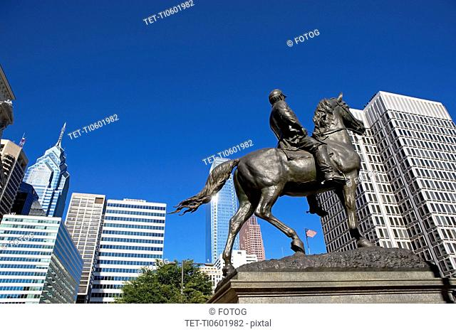 USA, Pennsylvania, Philadelphia, Statue depicting man on horse, skyscrapers in background